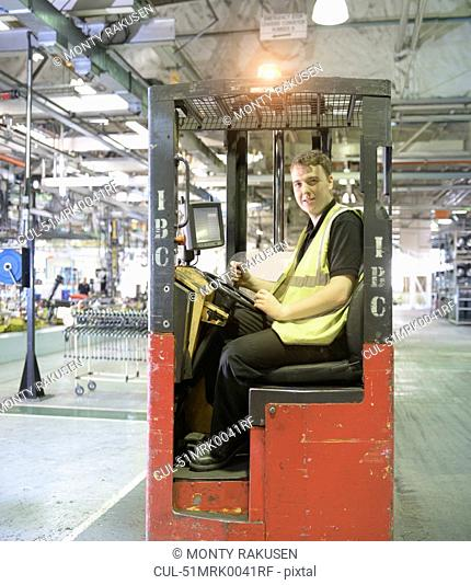 Apprentice lift operator in car factory