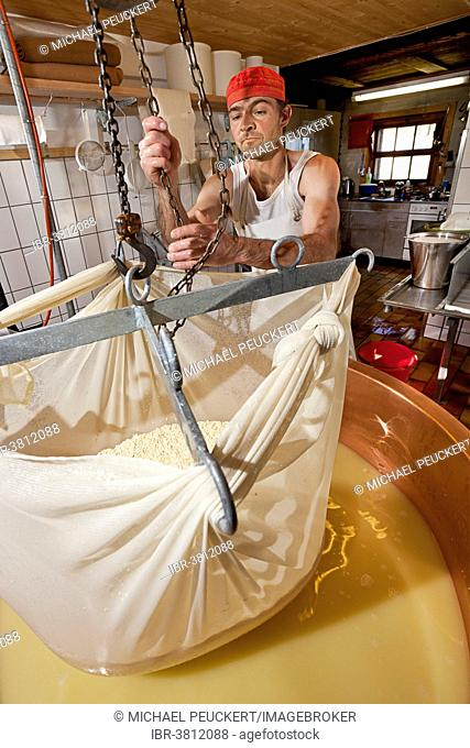 Dairyman raising the cloth with cottage cheese from the copper kettle to drain off the whey, Alp Gün, Graubünden, Switzerland