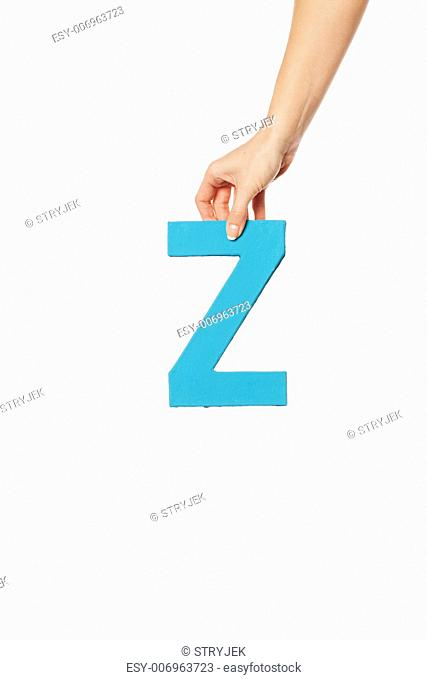 Female hand holding up the uppercase capital letter Z isolated against a white background conceptual of the alphabet, writing, literature and typeface