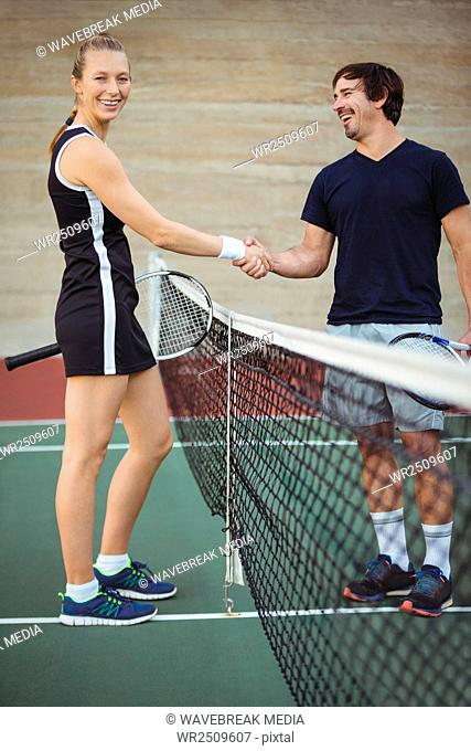 Tennis players shaking hands in the court