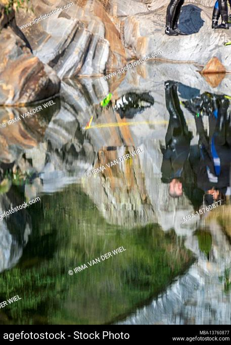 Switzerland, Ticino, Verzasca Valley, Verzasca, divers in the river at the popular basin with the granite rocks: reflection in the water