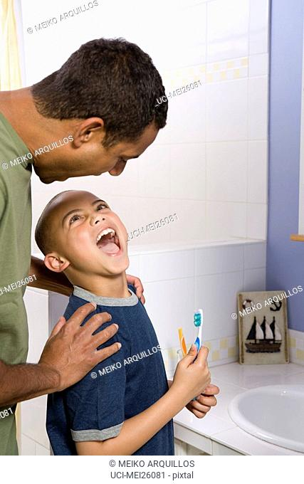 Boy showing his father his teeth