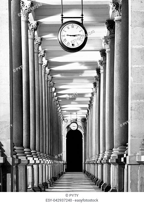 Long colonnafe corridor with columns and clock hanging from ceiling. Cloister perspective. . Black and white image