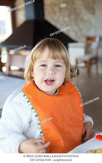 two years old blonde baby with orange bib looking and eating sitting in table of restaurant