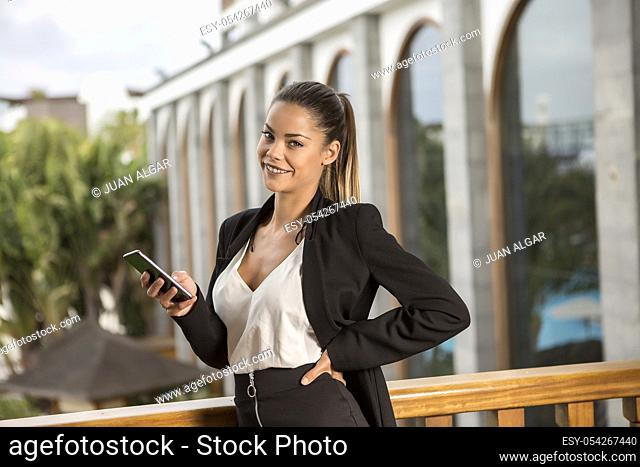 Beautiful smiling woman in elegant suit standing on balcony with smartphone and looking at camera on urban background