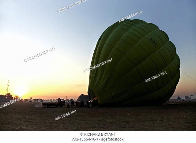 Hot air balloon inflating, at dawn, west bank Nile, at sunrise