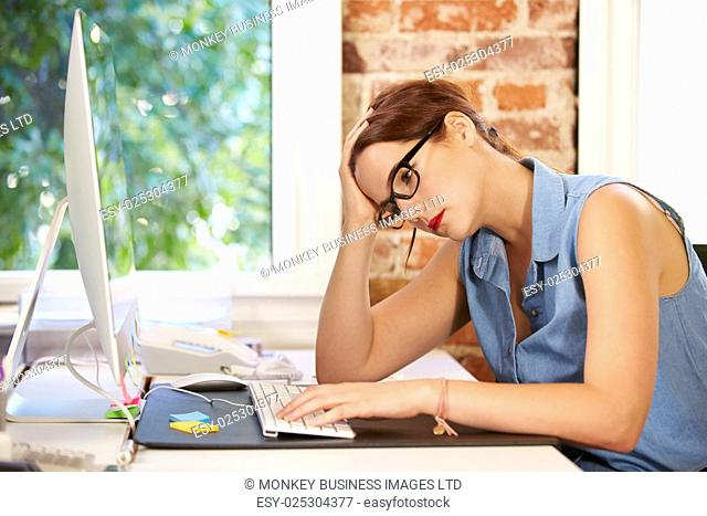 Stressed Businesswoman Working At Computer In Modern Office