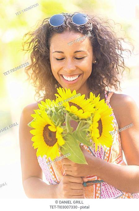 Portrait of smiling woman with sunflowers