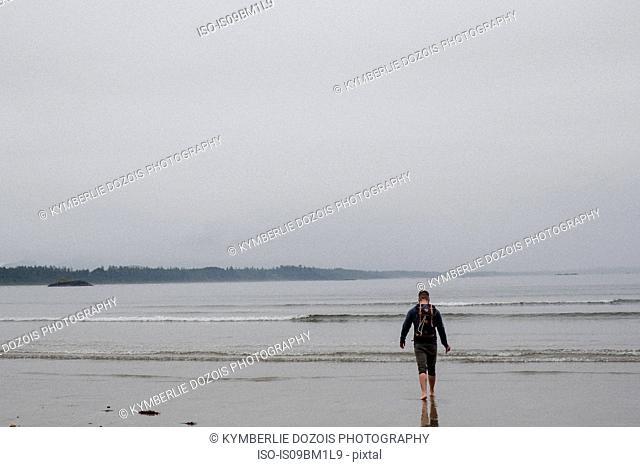 Man on beach, Tofino, Canada