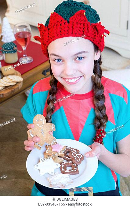 Young girl dressed as an Elf at Christmas Time. She is looking at the camera and smiling and is holding decorated gingerbread men