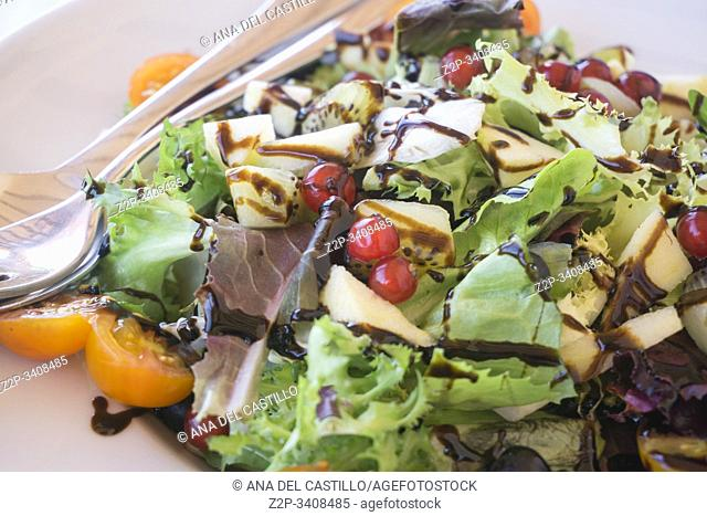 Fresh salad with apple red fruits and modena vinegar