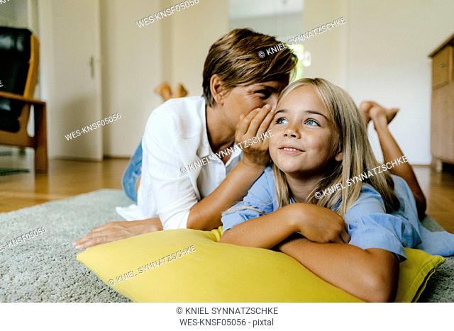 Mother and daughter lying on the floor at home whispering