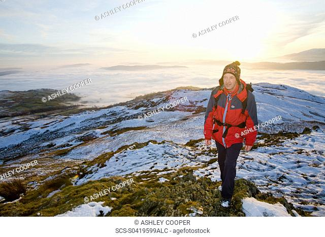 A walker on Wansfell Pike in the Lake District UK with valley mist below