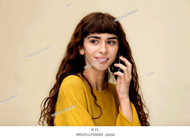 Portrait of young woman with freckles on the phone