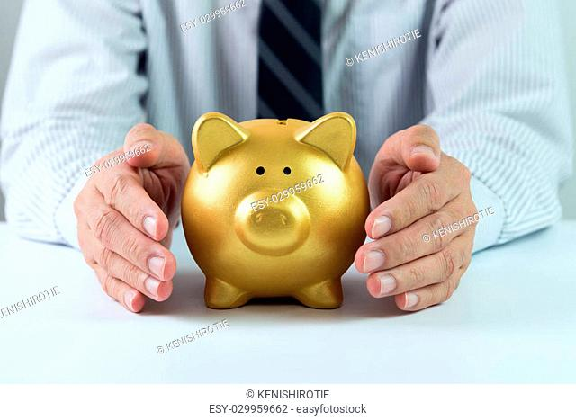 Protect your saving concept using hands covering golden piggy bank