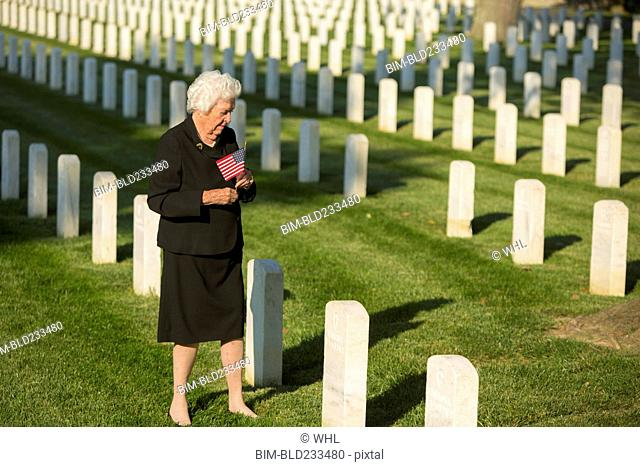 Caucasian widow holding American flag at cemetery gravestone