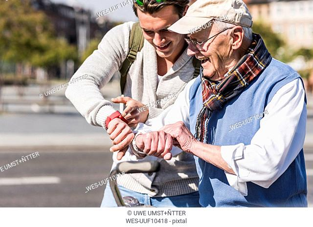 Happy senior man and adult grandson looking at their wrist watches