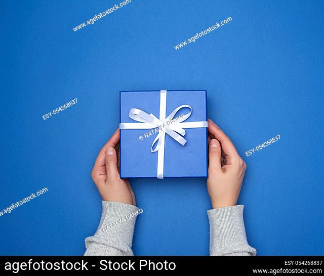 two female hands in a sweater hold a square blue box with a bow on a blue classic background, top view, festive backdrop
