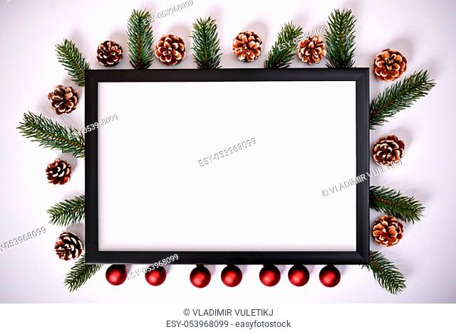 Christmas and New Year composition. Photo frame, pinecones, evergreen branches and decoration on white background. Christmas, winter, new year concept