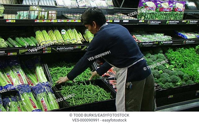 Man inspecting green beans in grocery store