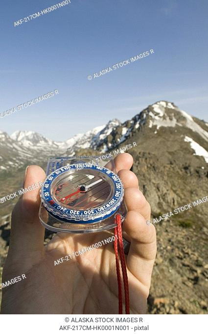 Hiker's hand holding a compass, pointing towards the mountains, Chugach Mountains, Southcentral, Alaska, Summer