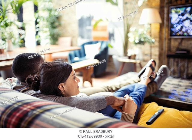 Affectionate young couple watching TV on living room sofa