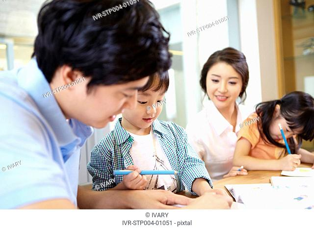 Father And Mother Helping Son And Daughter With Homework