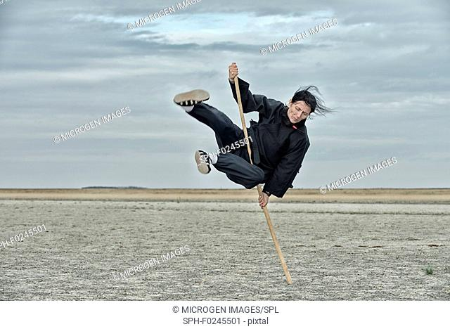 Woman doing qigong with stick