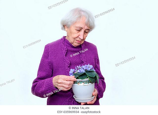 Mature woman holding violet flower in a pot isolated on white studio background