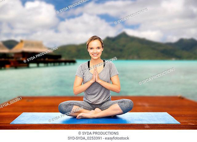 woman making yoga in and meditating lotus pose