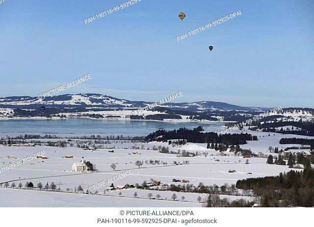 16 January 2019, Bavaria, Schwangau: Hot-air balloons are flying over Lake Forggen and the Sanctuary of St Coloman, which stands in a snow-covered landscape