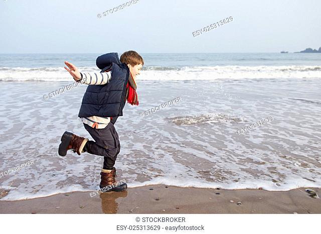 Young Boy Running Along Winter Beach