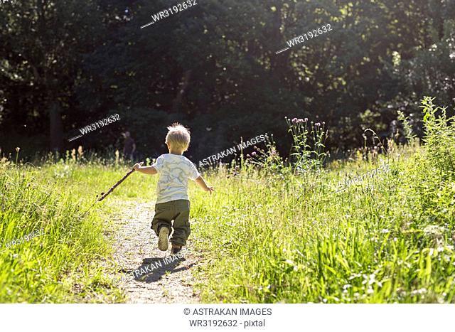 Boy (2-3) running on footpath