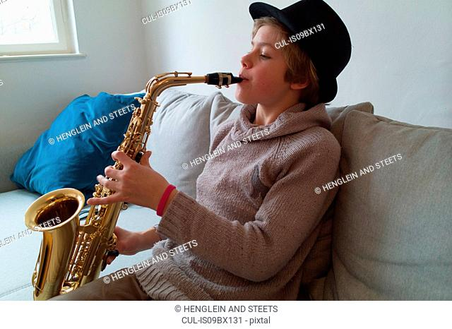 Boy practising saxophone on sofa