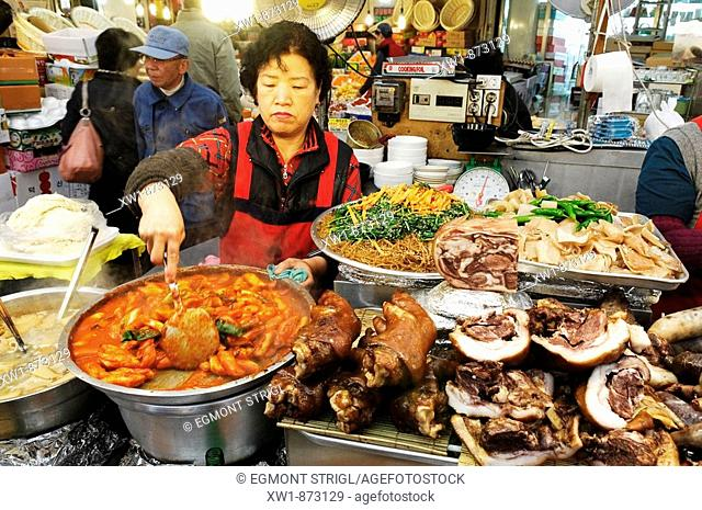 korean food, woman cooking in a small restaurant, food stall in a market in Seoul, South Korea, Asia