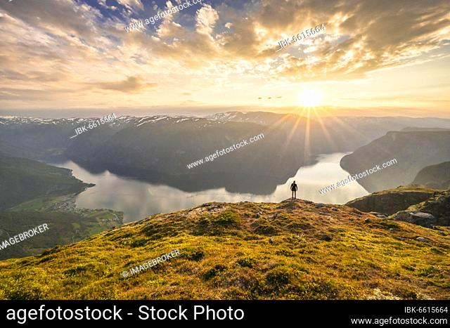 Hiker enjoying view, sunset on top of Prest mountain, Aurlandsfjord fjord, Aurland, Norway, Europe