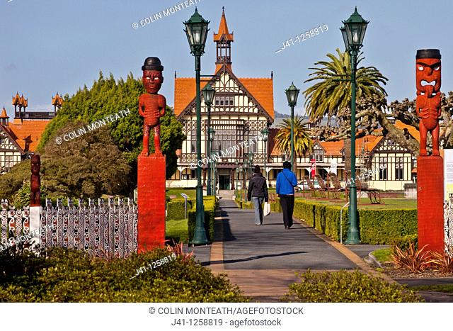 Rotorua Museum entrance pathway lined by lamps and Maori wooden carved figures, Government gardens, Rotorua