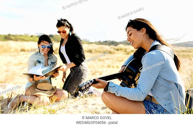 Young woman with friends playing guitar on the beach