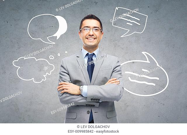 business, people and communication concept - happy smiling businessman in eyeglasses and suit over gray concrete wall background with text bubbles