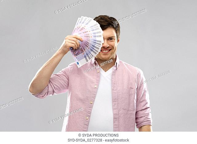 smiling young man with fan of euro money over grey