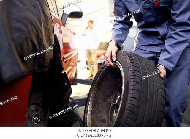 Mechanic replacing tire in auto repair shop