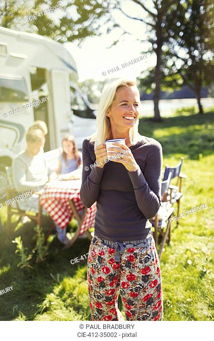 Smiling woman in pajamas drinking coffee outside sunny motor home