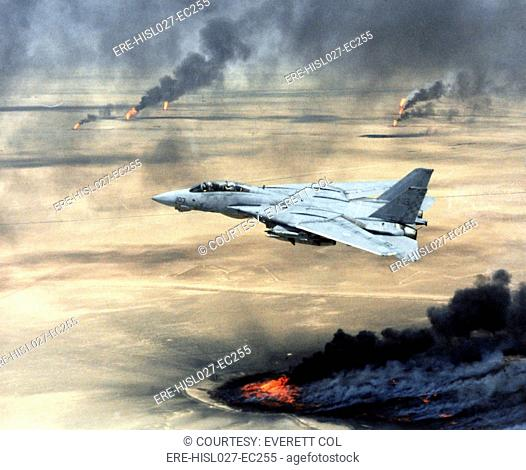 F-14 fighter in flight over burning Kuwaiti oil wells set on fire by retreating Iraqi forces during Operation Desert Storm. Mar
