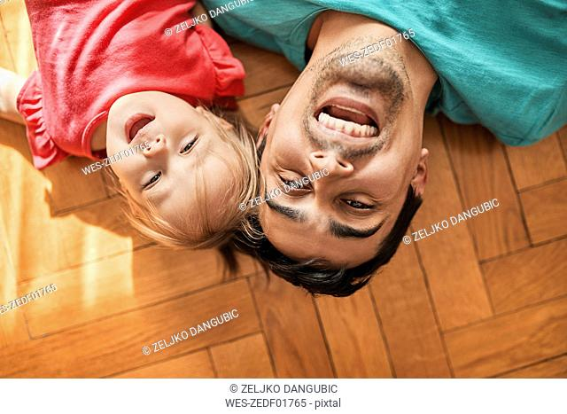 Portrait of father and little daughter lying on the floor at home having fun