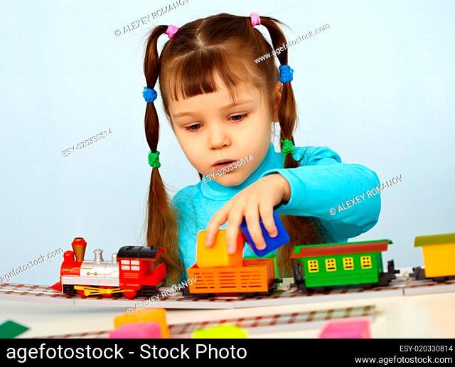 Little girl preschooler playing with toy railway