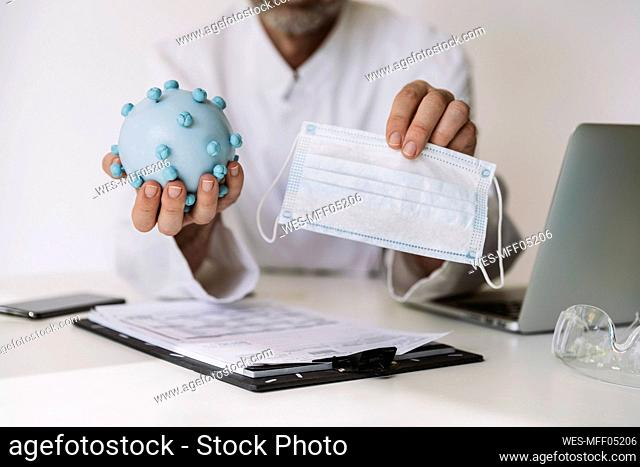 Close-up of scientist holding corona virus model and mask at desk