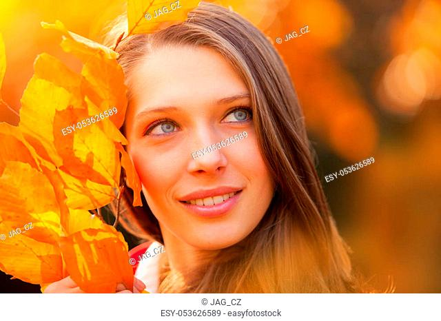 Beautiful young woman autumn portrait with colored leaves. Beauty and fashion photo, seasonal and holiday