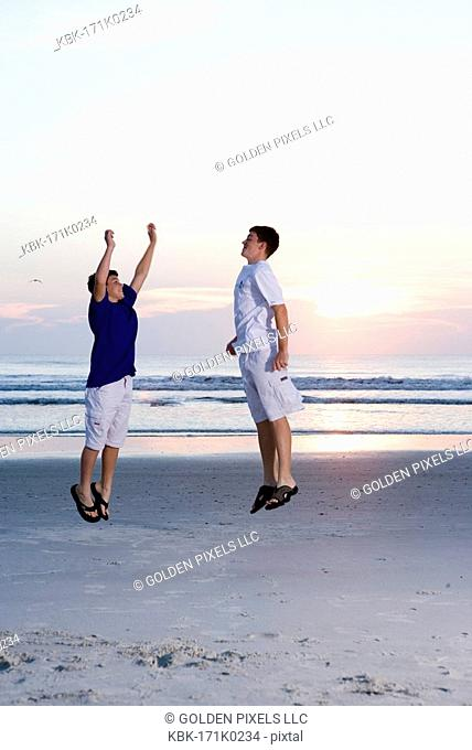 Two teenage boys playing and jumping on the beach at sunrise