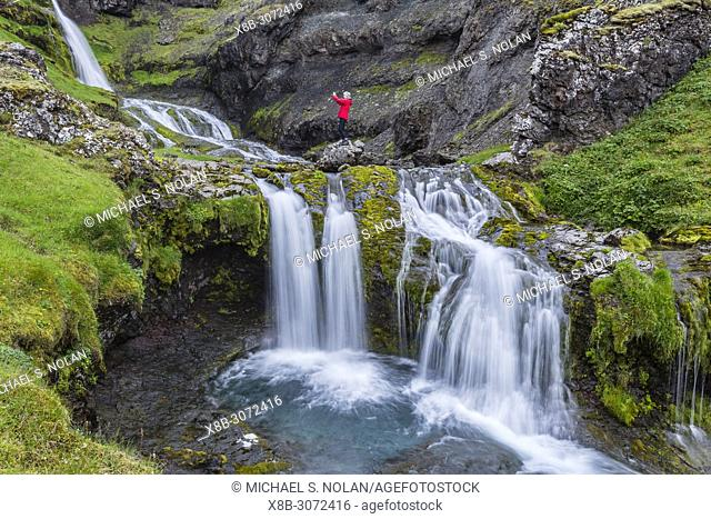 Photographer at small waterfall just outside the town of Grundarfjörður on the Snæfellsnes Peninsula, Iceland