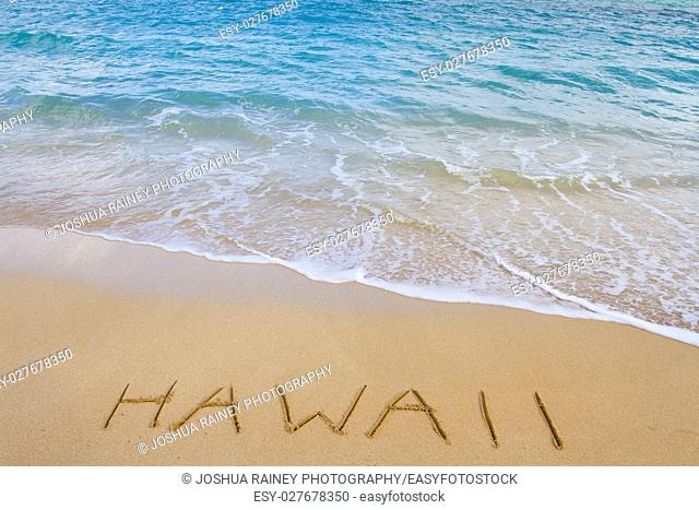 The word Hawaii is written in the sand of this beach as waves come in to wash it away. This is a vacation image showing the tropical location with sand and...